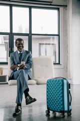 smiling businessman waiting at airport