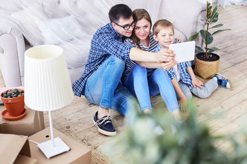 Adorable family of three gathered together in living room of new apartment and taking selfie on digital tablet, interior design items and moving boxes on background