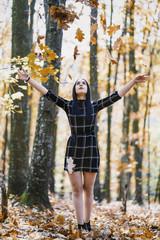 the brunette girl throwing the leaves upwards enjoying the autumn