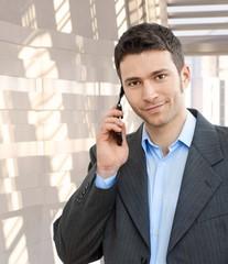 Portrait of happy businessman using mobile phone