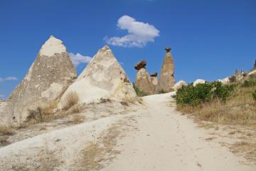Rocks looking like mushrooms dramatically lit by a sun in Chavushin in Cappadocia, Turkey.
