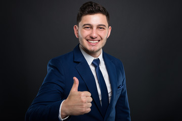 Smiling young businessman holding thumb up