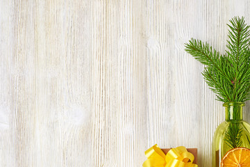 Christmas collection of tree branches, cones, green bottles, orange slice, gift box Kraf on a light wooden background