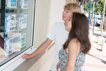 young couple in Real estate agency window display during day time