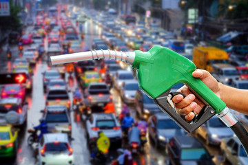 Right hands of men who were holding an automatic nozzle to make refill oil on traffic jam blurred background with concept idea about oil is also essential energy.