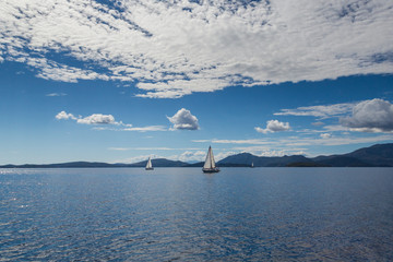 sailing boats on water with lefkas shore mountains and clouds blue sky