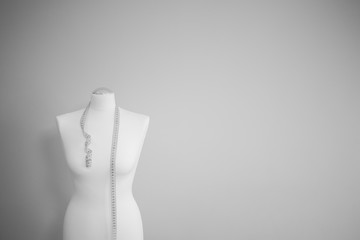 black and white picture of tailor dummy with measuring tape