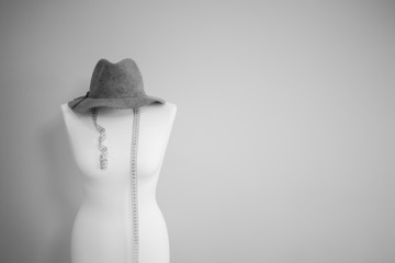 black and white picture of tailor dummy with measuring tape and vintage hat