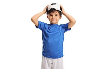 Little footballer holding a deflated football on his head