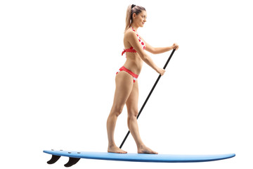 Young woman standing on a surfboard and paddling