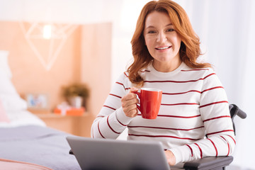 Being a freelancer. Attractive smiling blond disabled woman of middle age holding her cup and using her laptop while sitting in the wheelchair