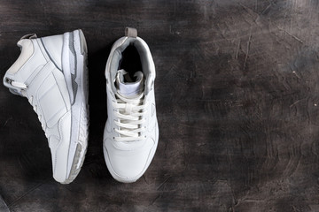 White sneakers on a dark concrete background. Place for the text. Copy space. Sale. Banner.