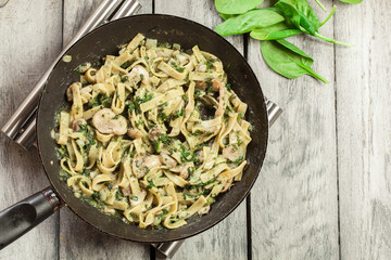 Tagliatelle pasta with spinach and mushrooms on a pan.
