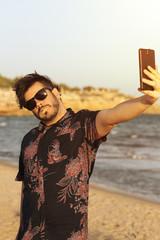 O homem feio usa camisa azul florida e oculos no dia ensolarado e quente na praia. Homem engraçado fazendo selfie com o seu telefone celular smart.