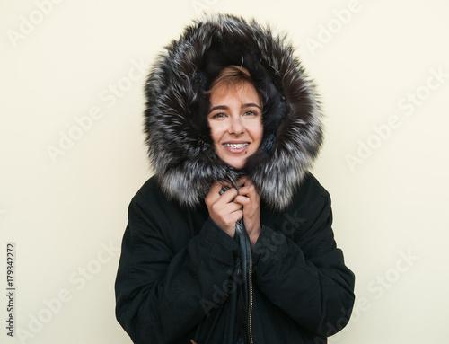 Hipster teen girl posing over wall,wearing warm casual fur