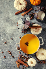 Ingredients for cook spicy pumpkin latte. Coffeepot, pumpkin milk in pan, jug of cream with spices, coffee beans and decorative pumpkins above over gray texture background. Top view, space.