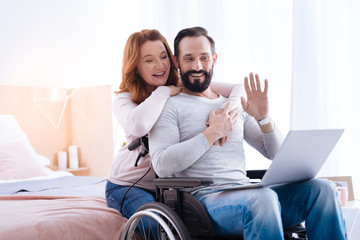 Having a conversation. Delighted blond woman of middle age and a bearded disabled man smiling and the man waving at the laptop while the woman hugging him and the man sitting in a wheelchair