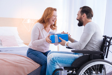 Gift for you. Paralyzed man and a laughing blond woman holding a present and looking at each other while the man sitting in a wheelchair and the woman sitting on the couch