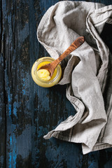 Glass of drawn ghee butter standing with wood spoon and linen textile over old dark blue wooden background. Healthy eating. Top view, copy space