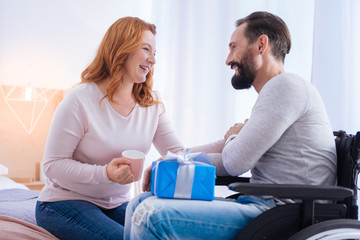 Everything for you. Loving and caring woman and a smiling disabled man looking at each other and laughing while she holding a cup and the man holding a present