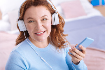 My hobby. Attractive blond dark-eyed woman of middle age wearing headset and holding her phone and wearing a blue sweater