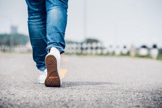 Close up woman wear jean and white sneaker walking forward on highway road in sunny day,Alone travel or solo traveler concept