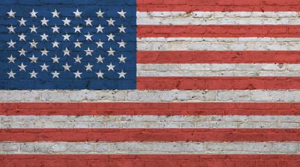 Old vintage American US flag over brick wall