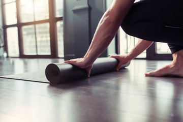 Yoga concept. Young men rolling mat after a yoga on black wooden floor