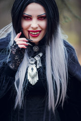 Photo of smiling vampire girl with stream of blood near mouth,