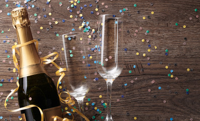 Photo of two wineglasses, bottle of champagne, confetti