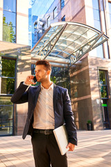 Young businessman standing in front of the office building and t