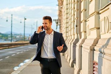 Young businessman walking on the street and talking on a phone