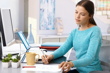 Casual young woman working home desk pen in hand