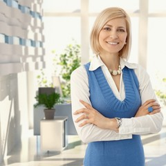 Elegant blond woman smiling at office
