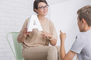 Female speech therapist showing letter