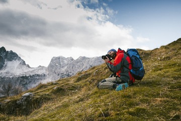 Mountain and nature photographer with his backpack and equipment on the mountain peak taking a photograph