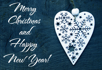 Merry Christmas and Happy New Year background with decorative christmas heart on dark blue wooden background.Selective focus.