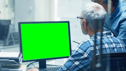Two Senior Architectural Engineers Working With Green Screen on a Personal Computer. They Actively Discuss Various Plans and Schemes. Great Template for Mock up.