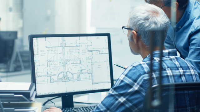 Two Senior Architectural Engineers Working With Building Blueprint on a Personal Computer. They Actively Discuss Various Plans and Schemes.