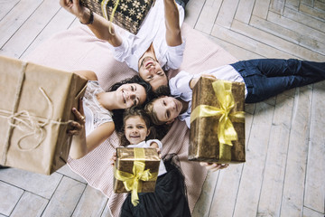 Beautiful happy family mother, father, son, and daughter with gifts in the hands are on the floor together at home