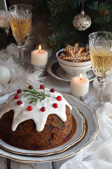 Traditional english Christmas steamed pudding with winter berries, dried fruits, nut in festive setting with Xmas tree, burning candle and glass of white wine, champagne. Fruit cake