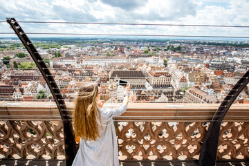 Young woman tourist photographing city view standing on the terrace of the main cathedral in Strasbourg city in Frace