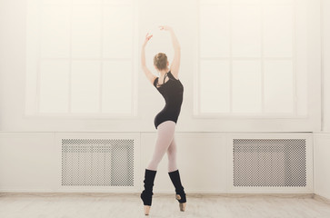 Beautiful ballerina stands in ballet croise