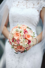 wedding bouquet of pion-shaped roses in the hands of brides, close-up, on a white dress background