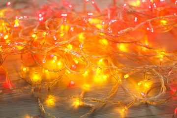 Christmas red and yellow lights border on light wooden background