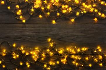 Christmas lights border on grey wooden background