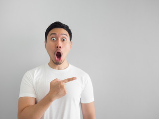 Shocked face of man in white shirt on grey background.