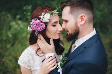 The pretty bride with a wreath of real flowers on her head gently kisses her fiance.