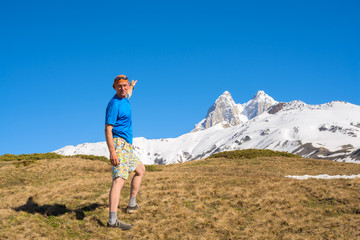 Joyful traveler walks along the mountain slope