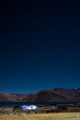 Landscape image of Pangong lake with mountains view and stars in the sky at nighttime